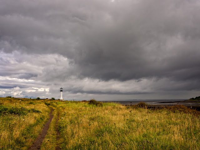 Photo of heavy clouds over a footpath to Maryport Lighthouse
