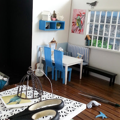 View of a one-twelfth scale cafe scene, with one corner perfectly arranged, and the rest of the room a mess of  various components and full-sized tools.
