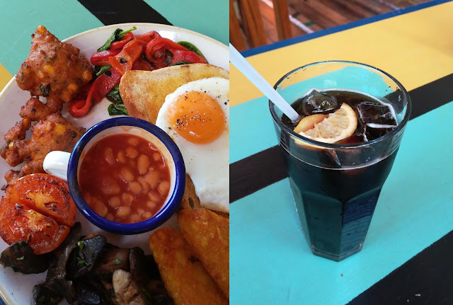 a plate of vegetarian brunch and glass of coke on a striped table