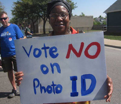 Woman holding hand-painted sign reading Vote No on Voter ID