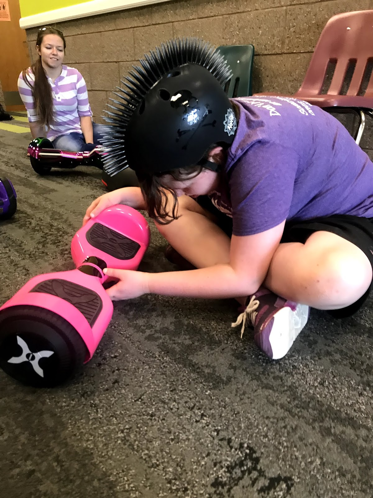 a female student wearing a fun helmet sits on the ground and checks out the hoverboard