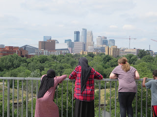 four young people gaze at the Minneapolis skyline