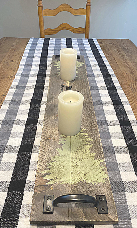 Wooden table runner on a farmhouse table with a buffalo check runner
