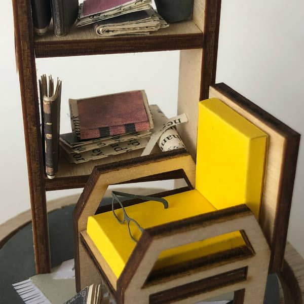 paper and wood library scene with chair, bookshelf, and books