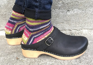 Person wearing hand-knitted wool socks with Dansko clogs