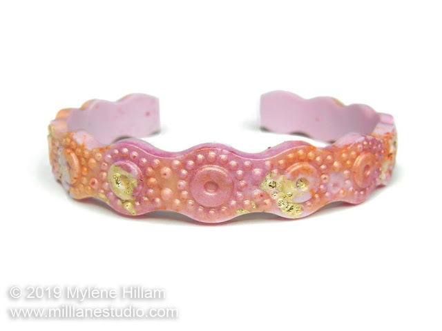 Pink and orange wavy resin bracelet with gold leaf flecks throughout.