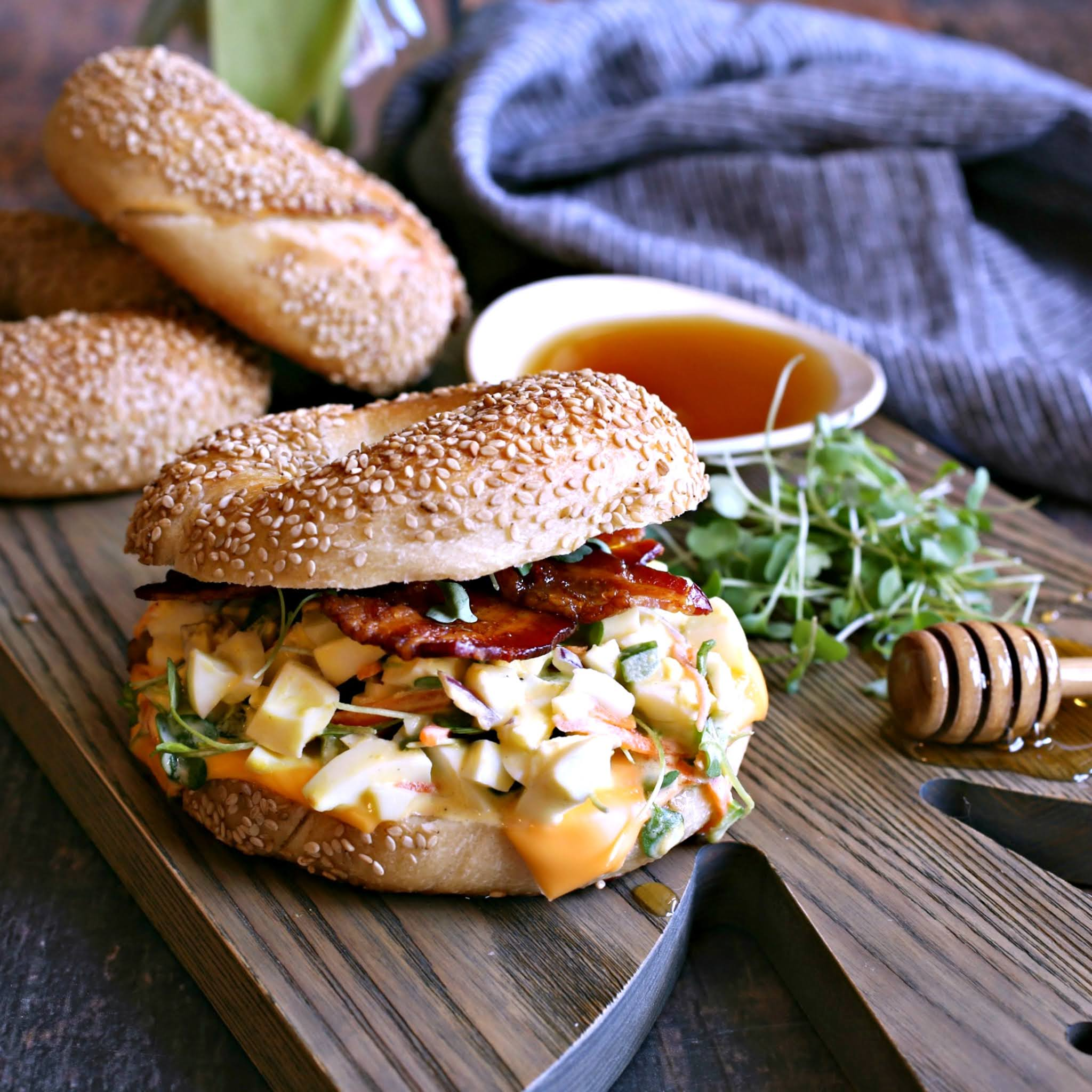 Recipe for an egg salad sandwich on a bagel, topped with bacon roasted with honey.