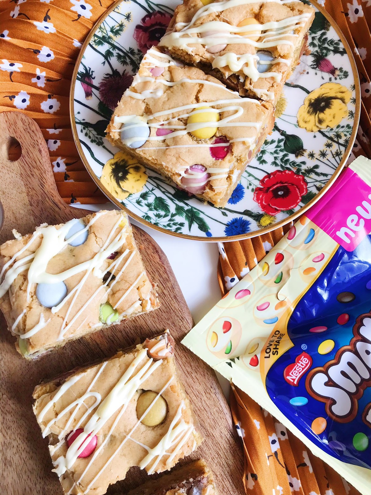 Smartie cookie slices on wooden chopping board net to flower trinket dish with cookie slice on, orange scarf as background