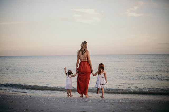 family standing on the beach on Sanibel at Sunset