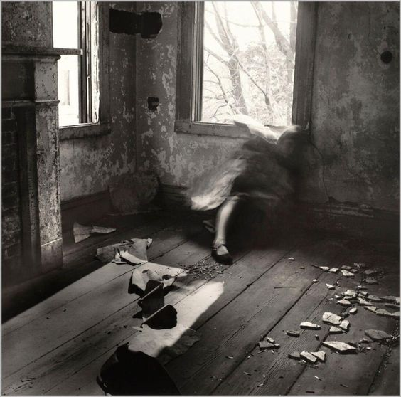 Black & White photograph of a woman whose top half is blured. Take by Francesca Woodman