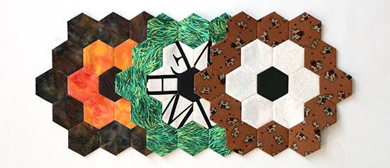 Three multi-colored EPP hexagon flower blocks overlapping in a horizontal row