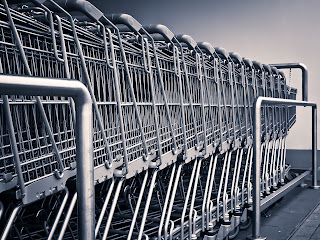a row of metal grocery shopping carts stacked together