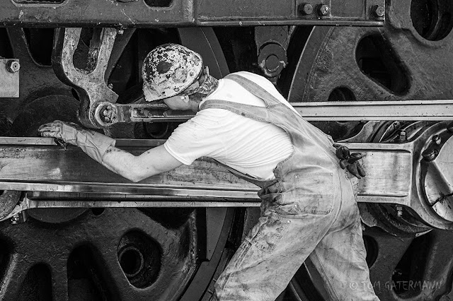 A member of UP 844's crea is cleaning and lubricating the locomotive's running gear.