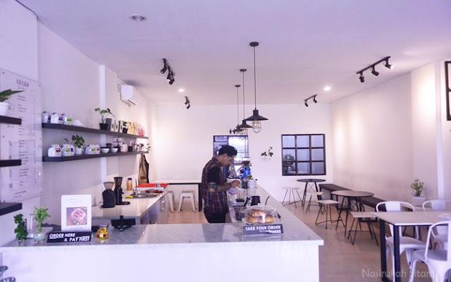 Meja dan kursi di dalam kedai Aegis Coffee