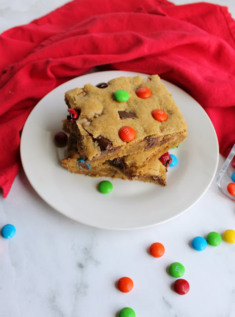 looking down on a couple of pieces of chewy salted caramel m&m blondies on plate with candies scattered around