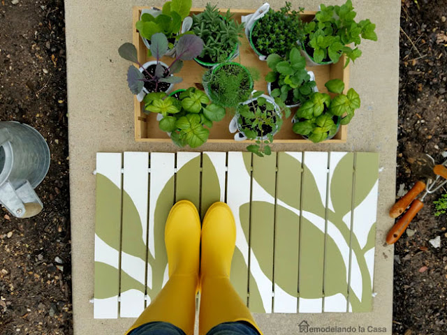 yellow rain boots on doormat with lots of green herbs to be planted.
