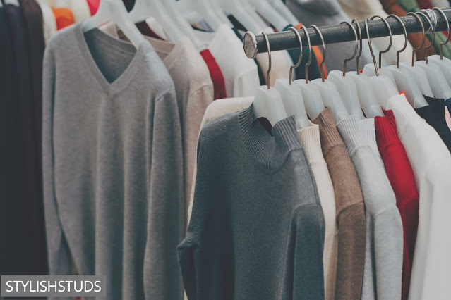 Many Men's sweaters hanging on hangers