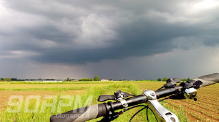 Una bici in mezzo ai campi e un grosso temporale in arrivo sullo sfondo