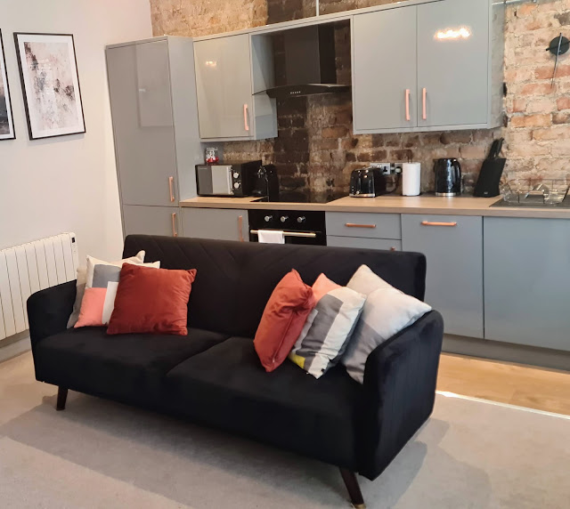 Image of the inside of Skippers Rest Holiday Rental. It shows the kitchen/living area which is a modern industrial style with exposed brick wall and grey gloss fitted kitchen. There is a black velvet sofa in the middle of the room and black and white art work on the walls.