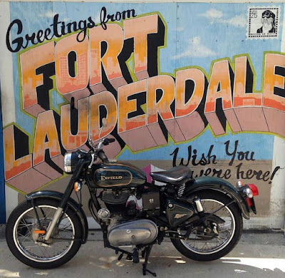 Royal Enfield motorcycle in front of Fort Lauderdale sign.
