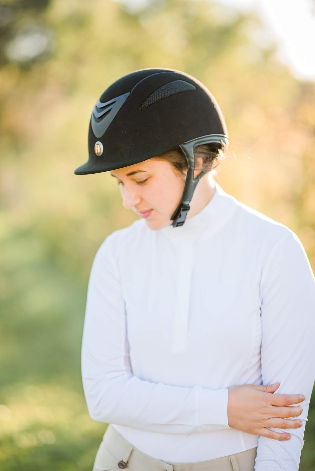Brunette girl wearing white long sleeve ROMFH show shirt with ovation riding breeches and One K Defender Suede Helmet at M and M Training Horse Barn in Saint Augustine Florida