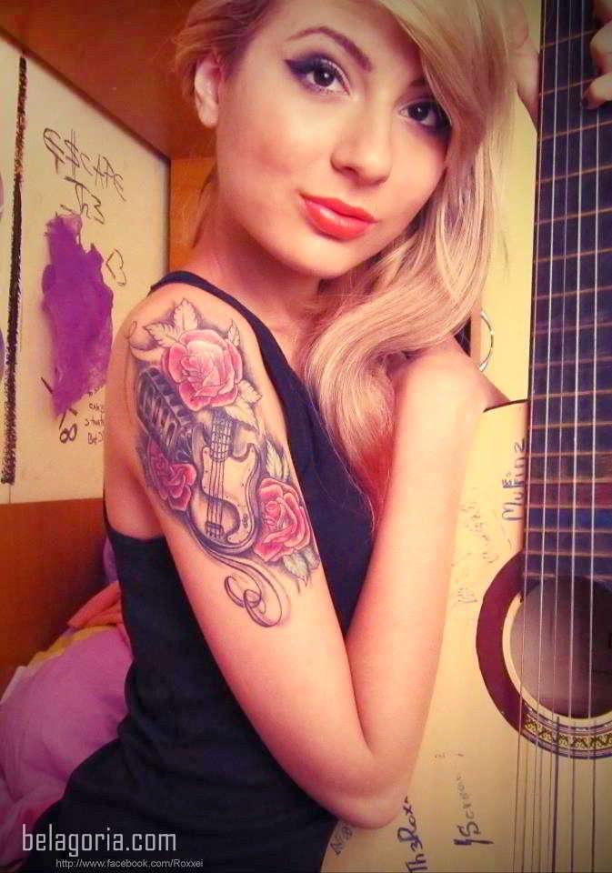 Imagen de una preciosa modelo rubia tatuada con un micrófono en el brazo