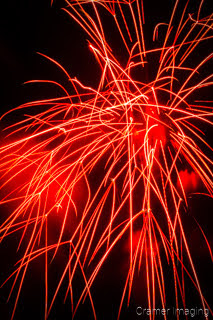 Badly-taken and timed photograph of a red firework exploding in the sky