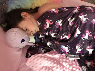 our youngest daughter lying in bed with her weighted blanket over her