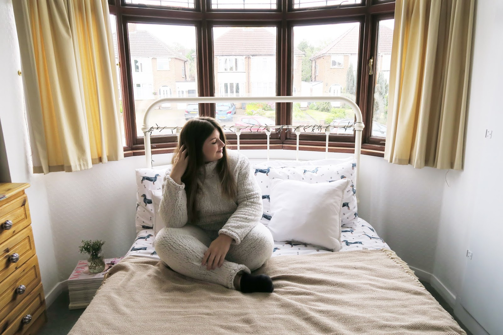 Grace can be seen sitting on her bed cross legged. She is wearing a thick fluffy set of grey pyjamas