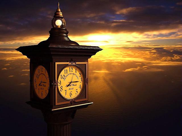 Una grande colonna orologio, sullo sfondo un tramonto con nubi dorate