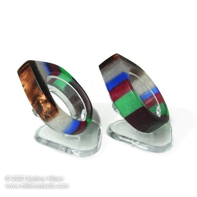 Two multicoloured striped resin rings viewed from the side to highlight the shimmering mica powder layers