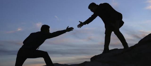 A imagem mostra uma pessoa ajudando outra a subir no cume de uma montanha, ao fundo vemos um lindo por do sol.