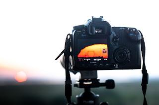 Fényképezőgép állványon napnyugta fotózásra beállítva