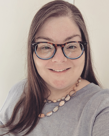 image of me from mid-chest up, wearing a lavender sweater, a stone necklace, and brown tortoiseshell glasses frames with blue highlights, with my hair down