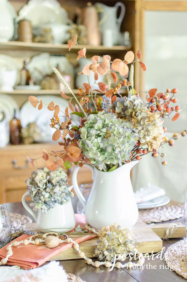 white stoneware pitchers with dried hydrangeas