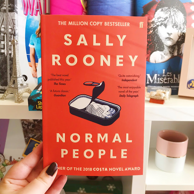 Normal People by Sally Rooney book held up in front of desk
