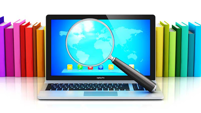 laptop with magnifying glass and books in background