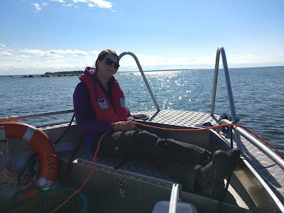 Henkilö istuu venen perässä ja pitelee sukellusnarua. Aurinko paistaa.