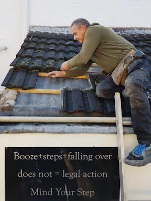 "Roofer up a ladder above pub sign ""Booze+steps+falling over does not = legal action. Mind Your Step"