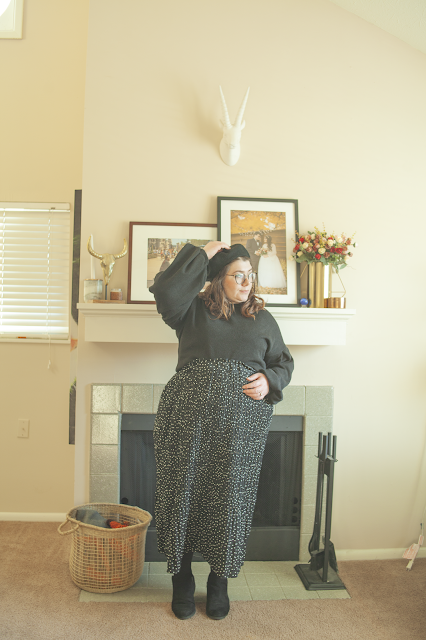 An outfit consisting of a black wool beret, black balloon sleeve tucked into a black and white micro dot maxi skirt and black ankle boots.