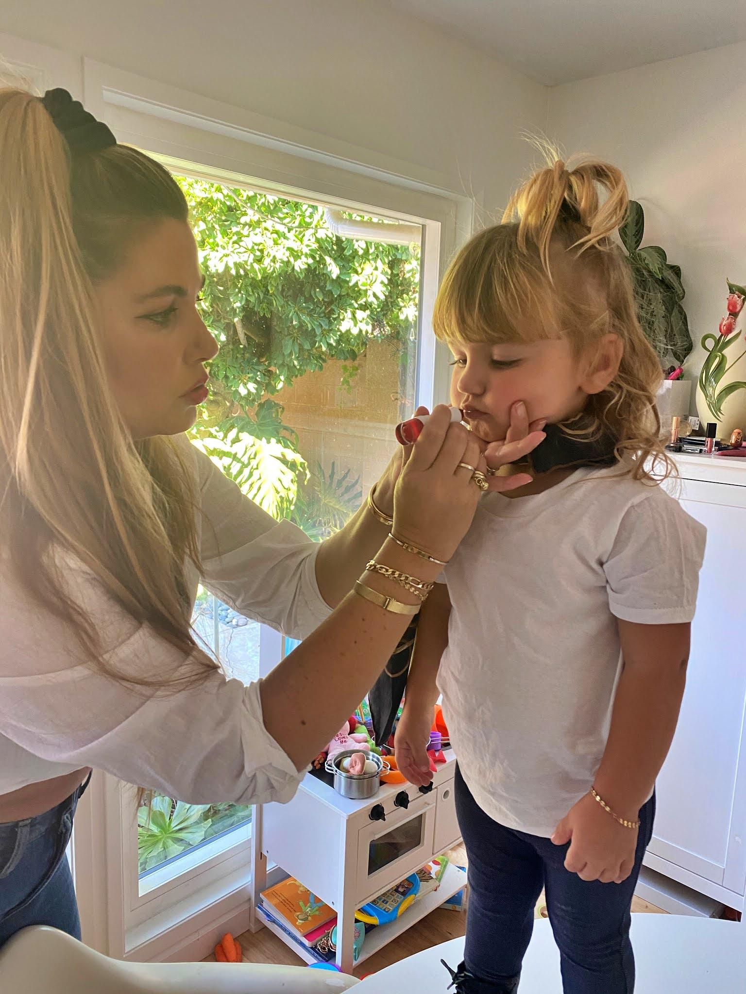 mom putting on lipstick on her kid