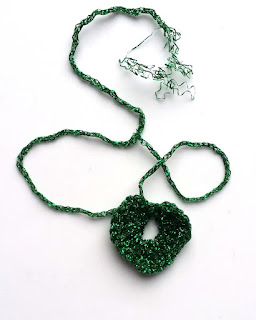 First attempt to crochet a shamrock leaf - a heart motif - resulted in an uneven shape with a large circle in the midle. The metallic yarn end is fraying at the top of the photo.