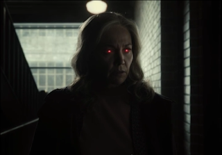 A shot of Martha Kent standing outside Lois's door with glowing red eyes.