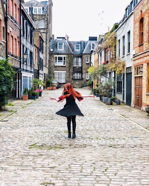 Photo of AJ twirling in a black dress with a Gryffindor scarf. Her hair is bright orange and she's standing in a cobbled mews in Central London with plants and coloured doors on either side.