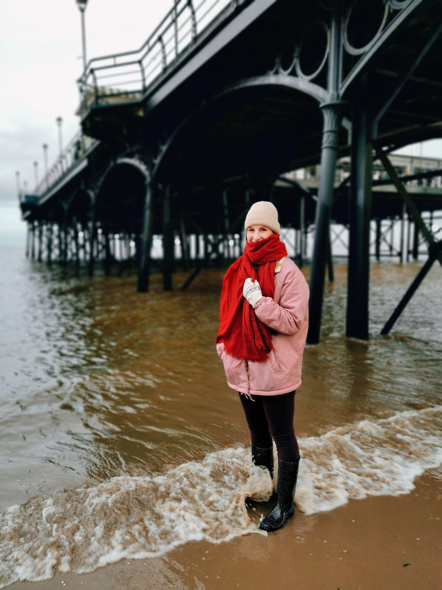 Amy is stood on the beach underneath a huge pier with water lapping at her wellies. She's wearing a pink coat and a red scarf.