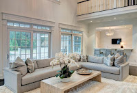Gray sectional sofa features fur rug and wood coffee table