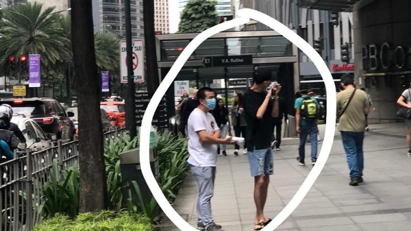 Two Chinese men give free facemasks to passersby in Makati