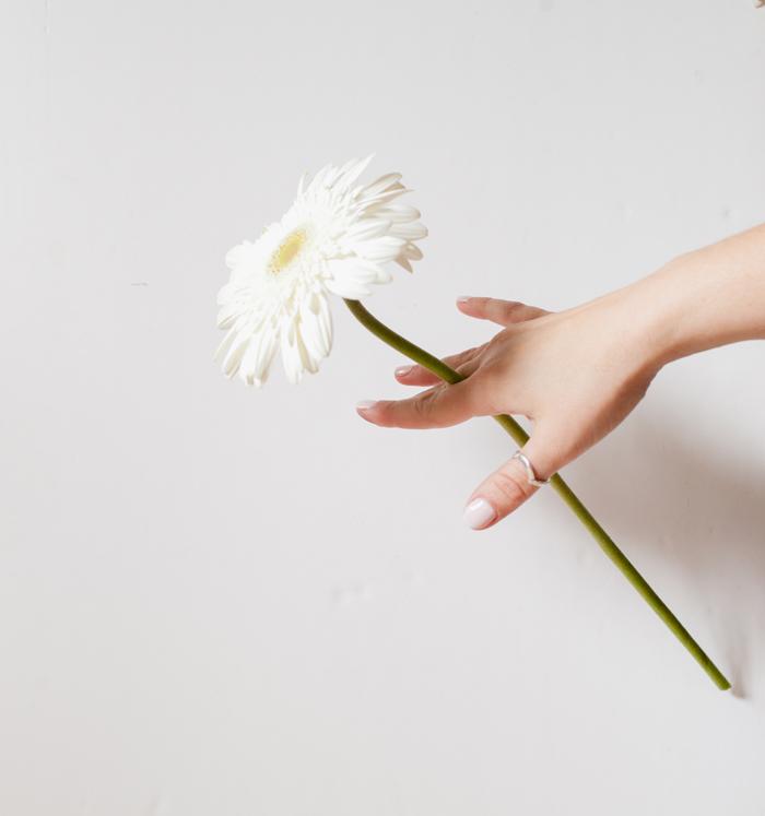 holding flowers between fingers
