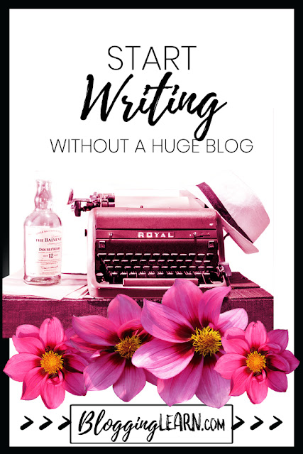 Start writing now without a huge blog featuring an old typewriter with a bottle of alcohol and some dahlias all in pink.