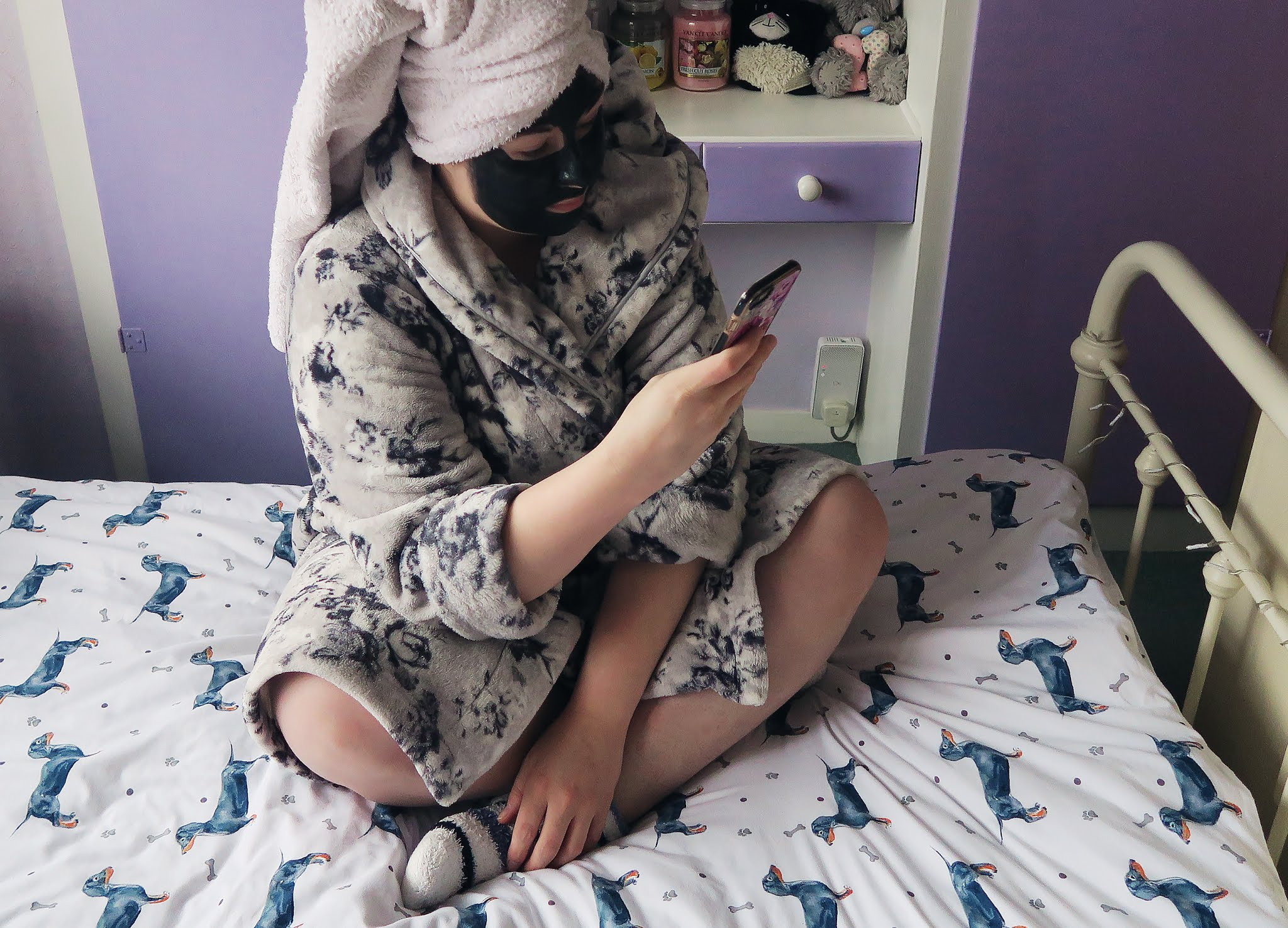 Grace is sitting on the bed in her dressing gown. Her hair is wrapped in a towel and she has a charcoal facemask on